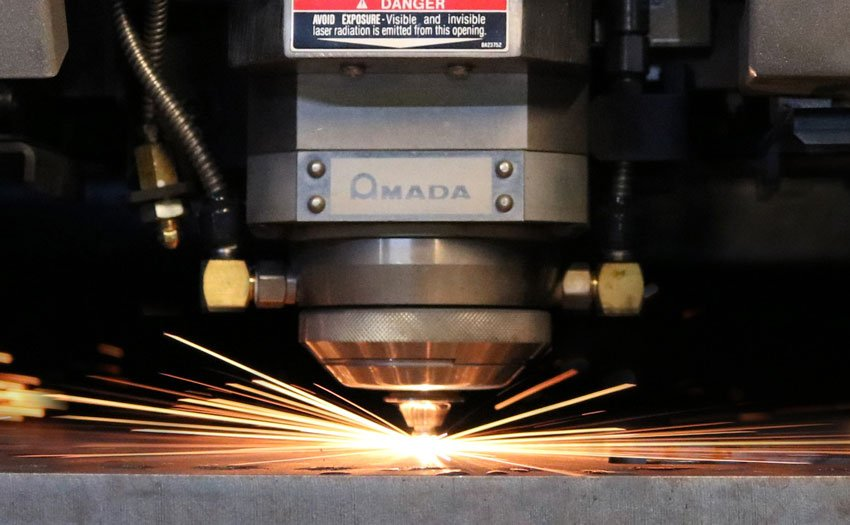 Sparks fly from the Amada 6000 watt laser cutter machining custom metal components